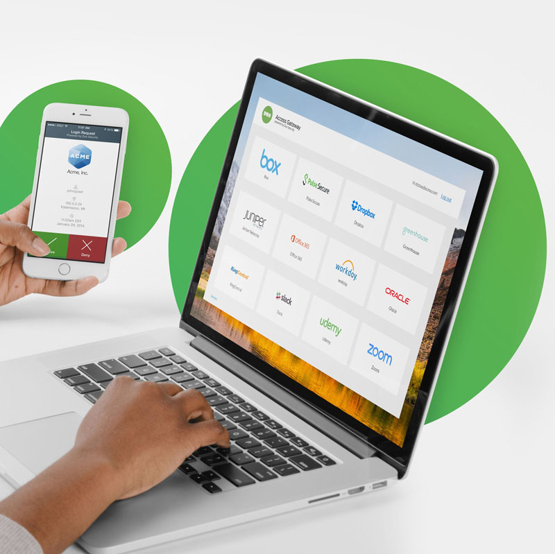 Close up of end user's hands holding a mobile phone displaying the Duo push app and using a laptop to log into applications.